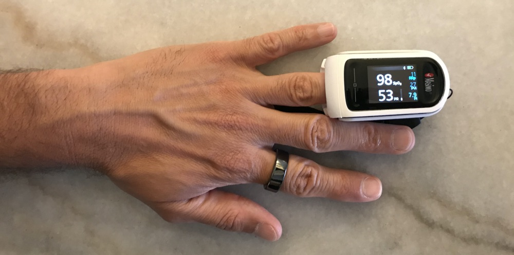 Fingertip pulse oximeter showing blood oxygen saturation and pulse rate